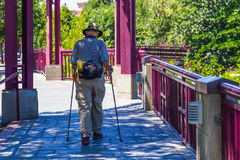 Aged Man With Walking Poles Walking For Exercise stock photo