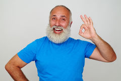 Aged man with white beard and broad smile showing OK gesture Royalty Free Stock Photos
