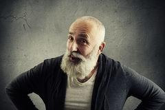 Aged man with white beard is posing with hands on hips against Stock Photos