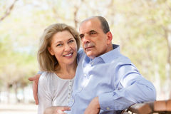 Aged man and woman hugging on a bench Stock Photos