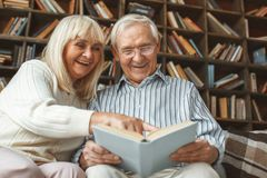 Senior couple together at home retirement concept reading book laughing stock photo