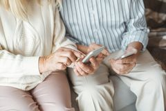 Senior couple together at home retirement concept sitting browsing smartphone touching close-up. Aged man and woman together at home in the living room sitting stock images