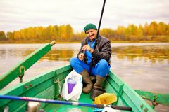 The aged man in wooden boat caught a little perch and smiles Stock Photography