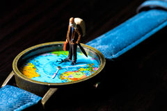 Aged man and world map travel watches. World travel photo banner. Senior traveler figurine. Retired backpacker travel. World time zone. Travelling around world Royalty Free Stock Photography