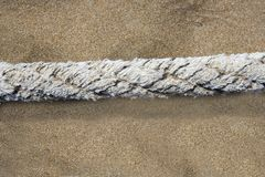 Aged marine rope over beach sand background Stock Photo