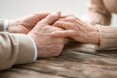 Aged married couple holding hands. Our union. Aged married couple sitting together while holding hands Royalty Free Stock Images