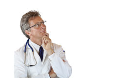 Aged medical doctor looks thoughtful up Royalty Free Stock Photos