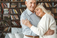 Senior couple together at home retirement concept standing head on shoulder. Aged men looking camera and woman`s head on his shoulder closed eyes together at royalty free stock photos
