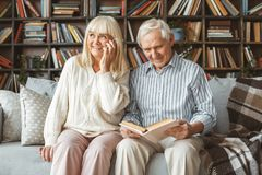 Senior couple together at home retirement concept phone call. Aged men reading book and women answering phone call smiling together at home in the living room stock photos