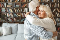 Senior couple together at home retirement concept dancing ballroom dance hugging cheerful. Aged men and women together at home in the living room dancing stock photography
