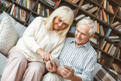 Senior couple together at home retirement concept sitting browsing smartphone touching. Aged men and women together at home in the living room sitting using stock image