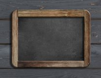 Aged blackboard hanging on black wooden wall 3d illustration Royalty Free Stock Photography