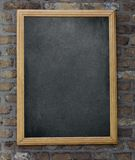 Aged menu blackboard hanging on brick wall Stock Images