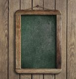 Aged menu blackboard hanging on wooden wall Royalty Free Stock Image