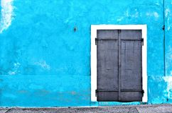 Aged metal door on blue wall - Warehouse Stock Photo