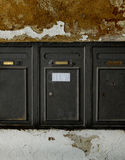 Aged metal mailboxes on old stone wall. Royalty Free Stock Photo