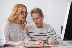 Aged office manager staring at young colleague at workplace. Harass at work. Ignorant playful mature manager sitting in the office and working on the project Royalty Free Stock Photo