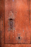 Aged old vintage door knob and keyhole. In weathered grunge red wood Royalty Free Stock Photo