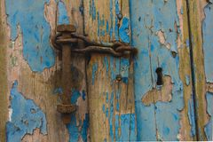 Aged old wooden door with peeling paint and rusty padlock stock photography