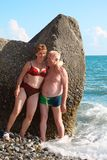 Aged pair at rock on sea beach royalty free stock photo
