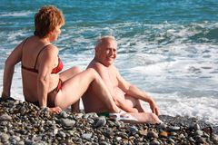 Aged pair sit on pebble beach Stock Images
