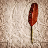 Aged paper with antique ink feather pen. Vintage style backgroun Royalty Free Stock Photo