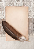 Aged paper, feather and linen fabric on the old wood Royalty Free Stock Photo