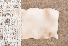 Aged paper with lacy cloth on sacking background Royalty Free Stock Photography