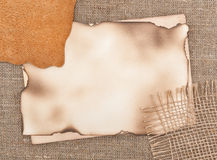 Aged paper with piece of leather on sacking background Stock Images
