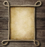 Aged paper with rope frame. On old wood background Stock Photo