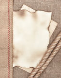 Aged paper with rope on sacking background Royalty Free Stock Photography