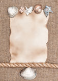 Aged paper with sea shells and rope on sacking background Stock Photos