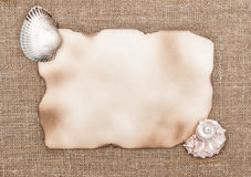 Aged paper with sea shells on sacking background Stock Images