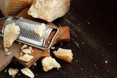 Aged parmesan cheese. On a wooden table close up stock photography