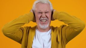 Aged pensioner covering ears suffering loud noise, conversation nervousness. Stock footage stock footage