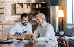 Aged person looking happy while showing an old photo to a volunteer Royalty Free Stock Photography