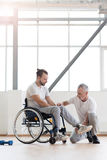 Aged physical therapist helping the disabled patient in the gym. Stretching the leg. Professional involved aged physical therapist helping the disabled men and Stock Photography