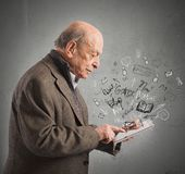 Aged reads books with tablet Royalty Free Stock Images