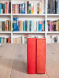 Aged red bound old books. On a wooden table with a book shelf full of books in soft focus behind royalty free stock photos
