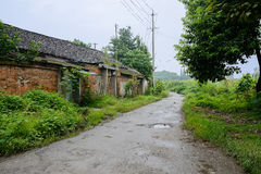 Aged red-brick dwelling houses along countryroad after rain Royalty Free Stock Photography