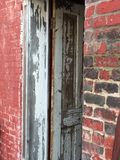 Aged red brick store front. With rustic white door entrance Royalty Free Stock Images