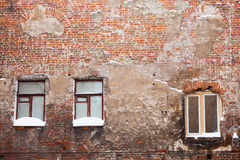 Aged red brick wall with windows. Snow on a window sill, winter time. Vintage red brick wall with windows. Snow on a window sill, winter time Stock Photography