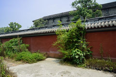 Aged red wall before Chinese traditional building on sunny day Stock Photography