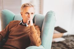 Aged retired businessman feeling concerned. Concerned businessman. Aged retired prosperous businessman feeling very concerned while thinking about future of his royalty free stock photography
