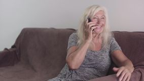 Aged retired woman talking on the phone. Portrait of a grandmother speaking with a telephone and seating on the sofa stock video