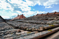 Aged roofing tiles on old house in village on blue cloudy sky Stock Photo