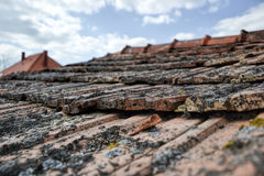 Aged roofing tiles on old house in village on blue cloudy sky Stock Images
