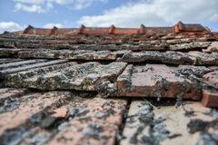 Aged roofing tiles on old house in village on blue cloudy sky Royalty Free Stock Photos