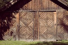 An aged, rural farm building with two doors and rusted locks with a rustic natural wooden facade and decorative woodwork stock photography