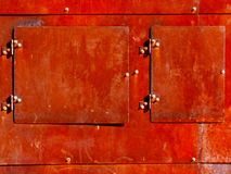 Aged rusty exterior steel plate access door detail. Aged rusty facade detail with mechanical access doors, shadow and galvanized fastener royalty free stock photo